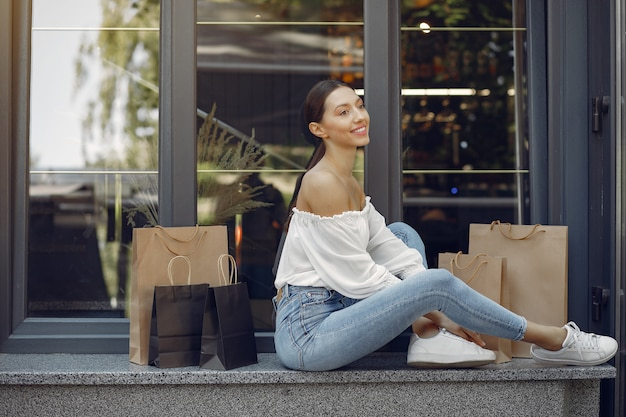 Elegant and stylish girls in the street with shopping bags Free Photo