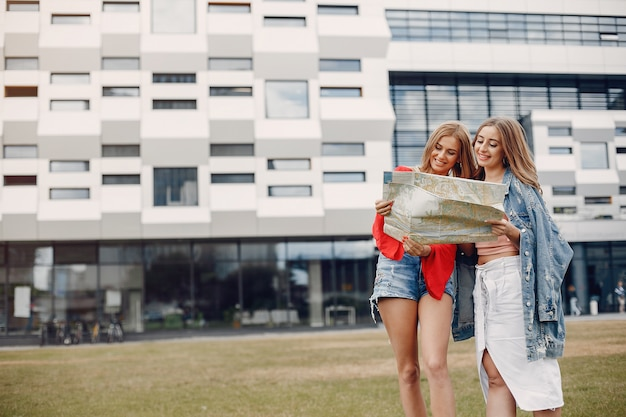 Elegant and stylish girls in a summer park Free Photo