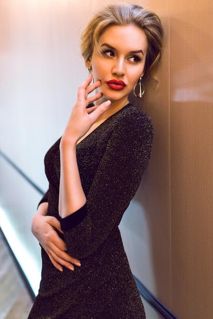 Elegante signora alla moda che indossa un abito scintillante da sera lungo in posa nel corridoio dell'hotel, effetto film, colori tenui tonica, vita di lusso. Foto Gratuite