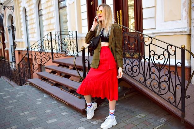 Elegante donna bionda alla moda in posa sulla strada vicino al bellissimo edificio antico, parlando dal suo telefono, indossando occhiali da sole e abbigliamento alla moda alla moda hipster, stile primavera autunno. Foto Gratuite
