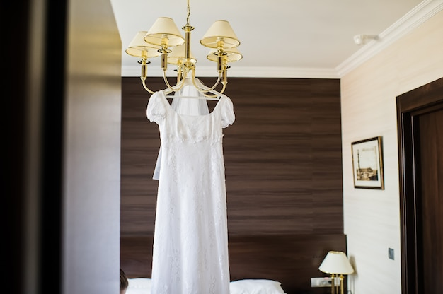 Elegant wedding dress hanging on the chandelier in the interior of the hotel Premium Photo