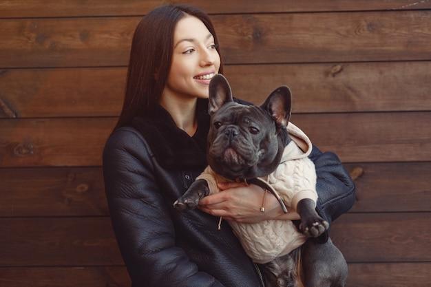Elegant woman in a black jacket with black bulldog Free Photo