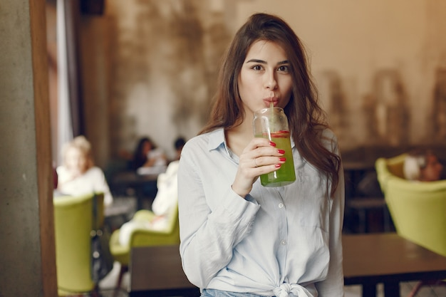 Elegant woman in a blue blouse spending time in a cafe Free Photo