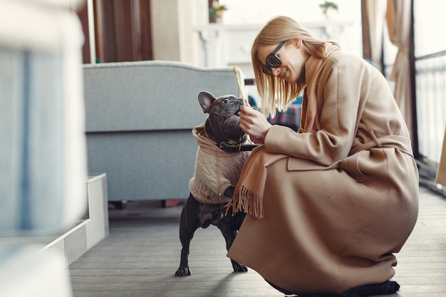 Elegant woman in a brown coat with black bulldog Free Photo
