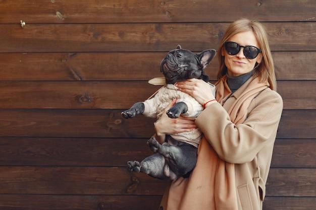 Elegant woman in a brown coat with black bulldog Free Photo