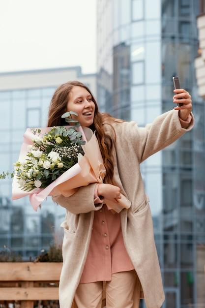 Donna elegante che tiene il mazzo di fiori all'esterno e prendendo selfie con lo smartphone Foto Gratuite