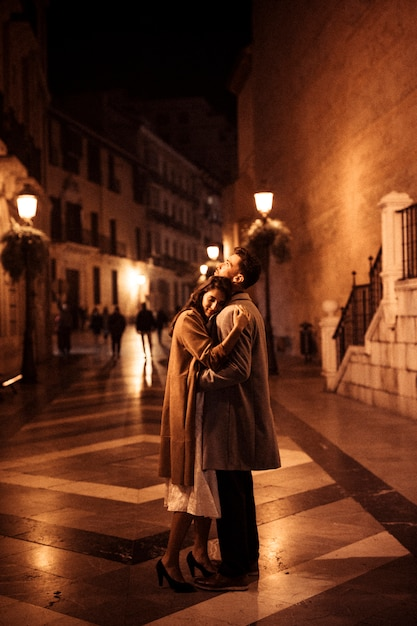 Elegant woman hugging with young man on promenade in evening Free Photo