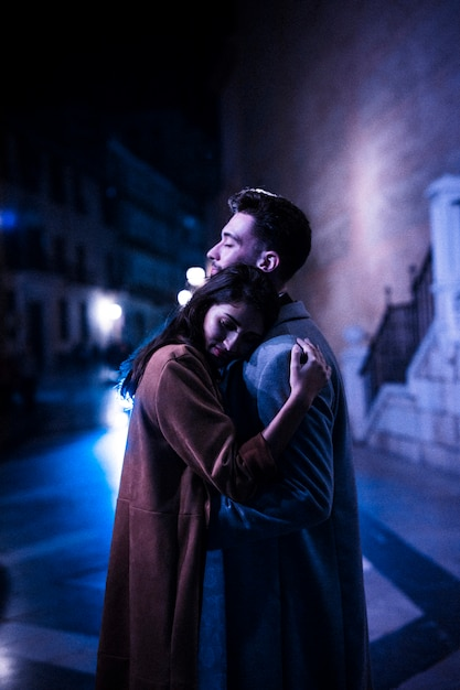 Elegant woman hugging with young man on promenade at night Free Photo