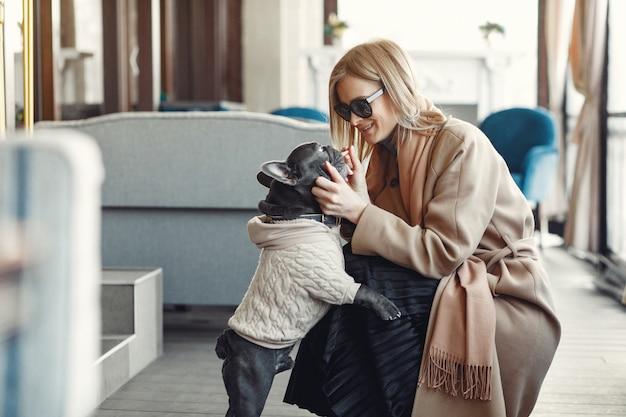 Элегантная женщина в коричневом пальто с черным бульдогом Бесплатные Фотографии