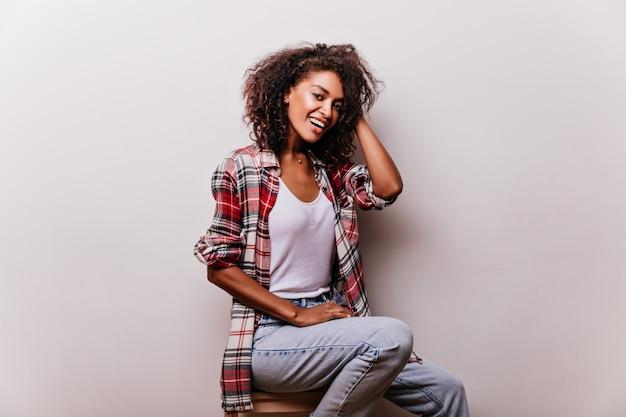 笑顔のヴィンテージブルージーンズのエレガントな女性。ショットシュートを楽しんでいるカジュアルな服装でスタイリッシュなアフリカの女の子。 無料写真