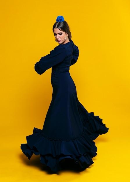 Elegant woman looking down with orange background Free Photo