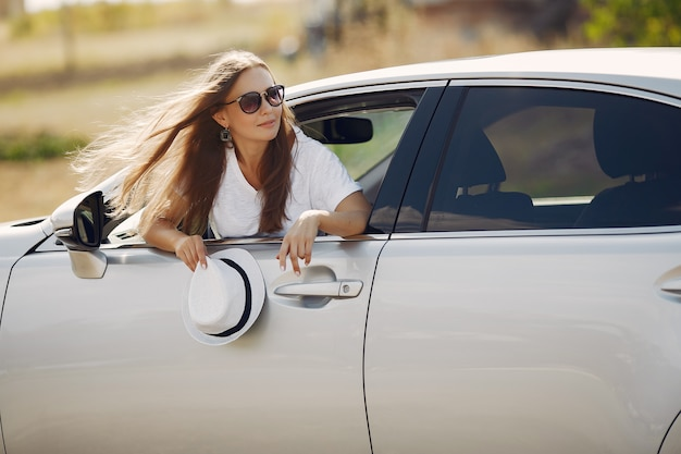 Elegant woman looks out of the car window Free Photo