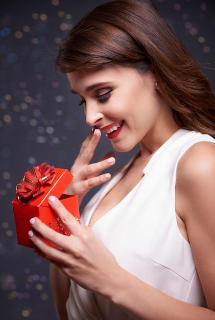 小さなクリスマスプレゼントを開くエレガントな女性 無料写真