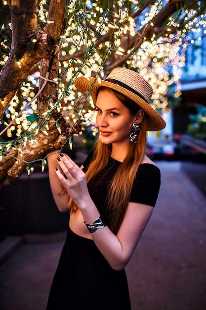 Элегантная женщина позирует на террасе роскошного отеля возле дерева с праздничными огнями Бесплатные Фотографии