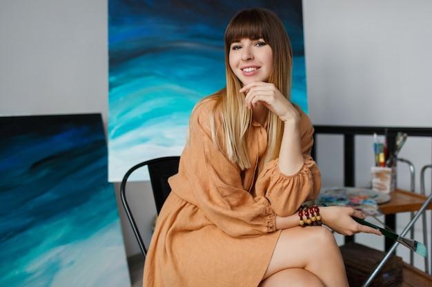 エレガントな女性が新しい彼女のアート作品でポーズします。 無料写真