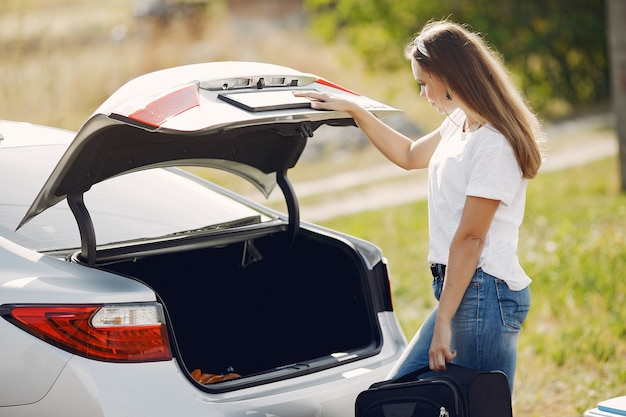 Elegant woman removes the suitcase from the trunk Free Photo