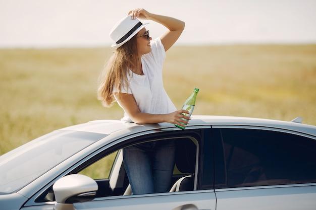 車のハッチに立っているエレガントな女性 無料写真