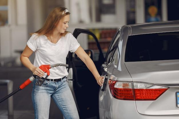 ガソリンスタンドに立っているエレガントな女性 無料写真