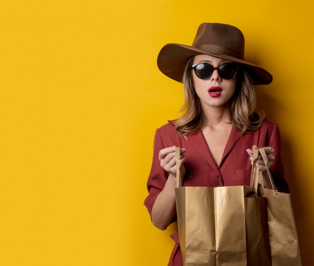 Elegant woman in sunglasses and with shopping bags Premium Photo