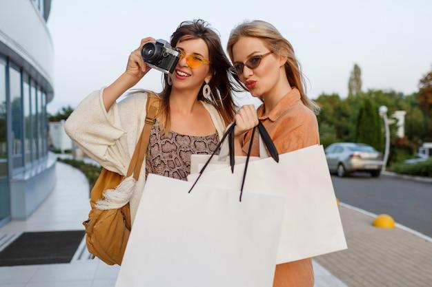 旅行を終了し、空港の近くに屋外のポーズのショッピングの後のエレガントな女性 無料写真