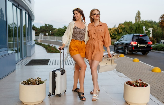 Elegant women after exiting trip and shopping posing outdoor near airport Free Photo