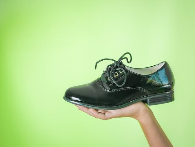Elegant women's shoe in hand on green Premium Photo