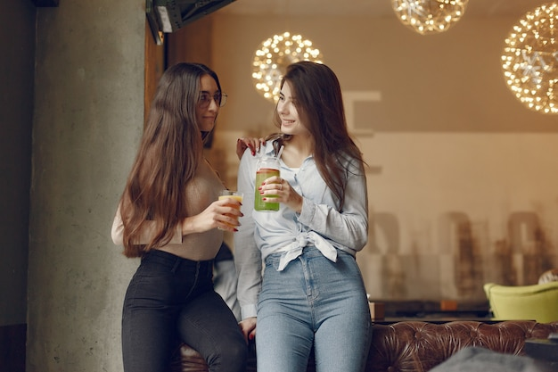 Elegant women standing in a cafe and drinking a cocktails Free Photo