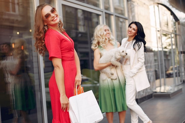 Elegant women with shopping bags in a city Free Photo
