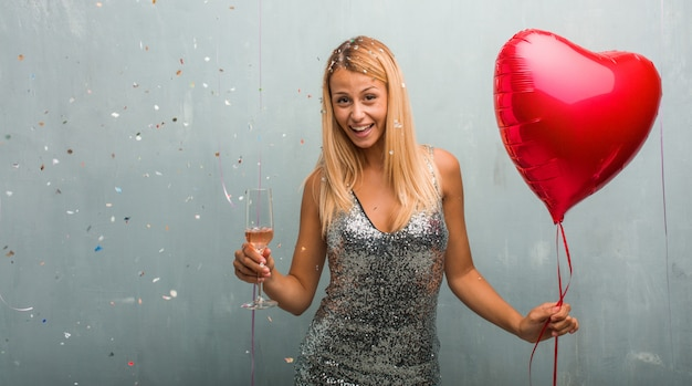 Elegant young blonde woman celebrating an event, holding a champagne cup and a red heart balloon. Premium Photo
