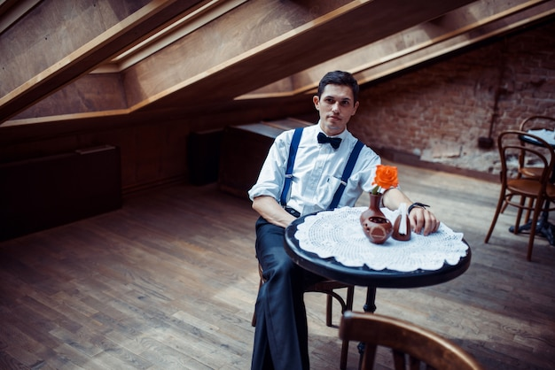Elegant young man in suspenders and glasses in cafe Premium Photo