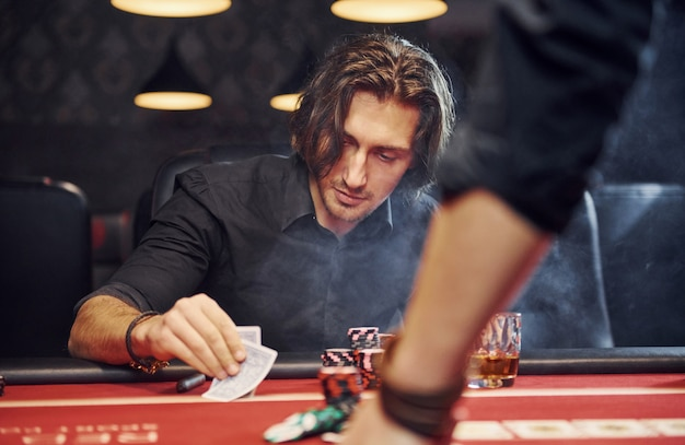 Elegant young people sits by table and playing poker in casino with smoke in the air Premium Photo