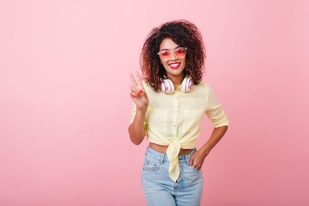 新しい服でポーズをとる機嫌の良いエレガントな若い女性。アフリカの髪型を持つかっこいい愛らしい女の子。 無料写真