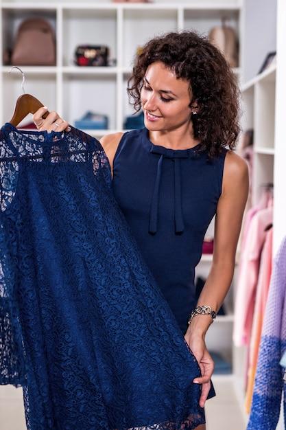 Элегантная молодая женщина ищет новое платье в магазине одежды Premium Фотографии