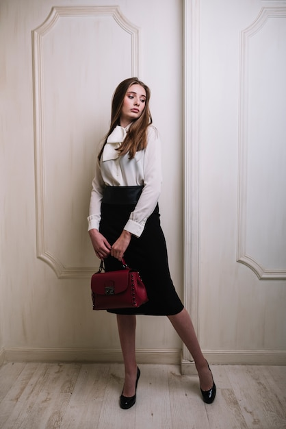 Elegant young woman in skirt and blouse with handbag in room Free Photo