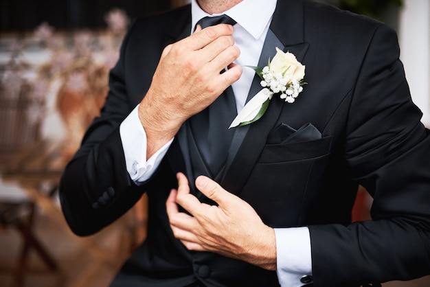 Elegnat groom in black stylish suit putting on a tie in the morning before the wedding. Premium Photo