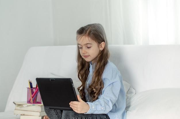 Una ragazza della scuola elementare si siede a casa sul divano con un laptop in una lezione online durante la quarantena a causa della pandemia di coronavirus. Foto Gratuite