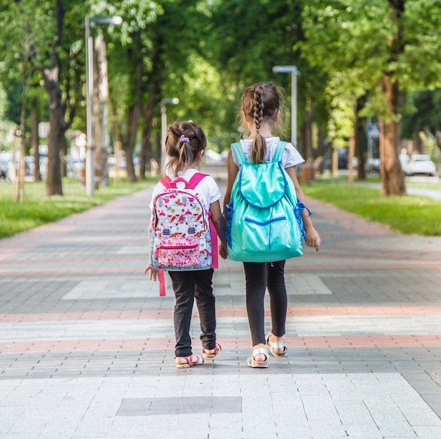 Elementary students, carrying backpacks going to class Free Photo