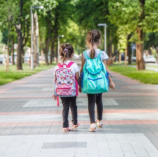 Учащиеся начальной школы с рюкзаками идут в класс Бесплатные Фотографии