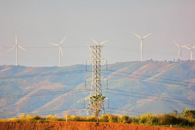 電柱は風力タービンから自宅、町、市への移動から電流を取得します Premium写真