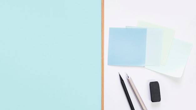 Elevated view of adhesive notes; pen; pencil and eraser on desk Free Photo