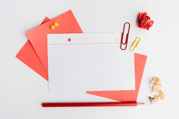 Elevated view of adhesive notes; pencil; paperclip and crumpled paper Free Photo