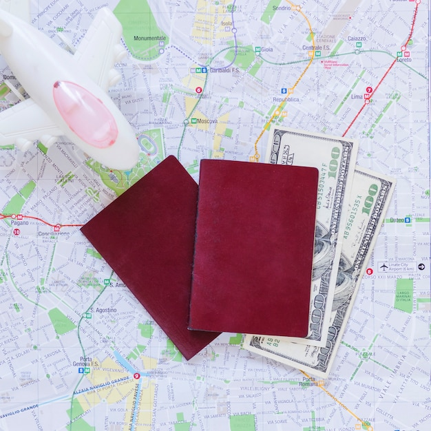 Elevated view of airplane; passport; banknotes and map Free Photo