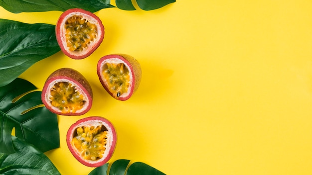 An elevated view of artificial green leaves and halved passion fruits on yellow background Free Photo