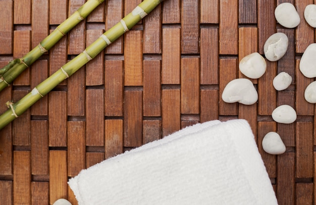 Elevated view of bamboo plant; white towel and pebbles on wooden floor Free Photo