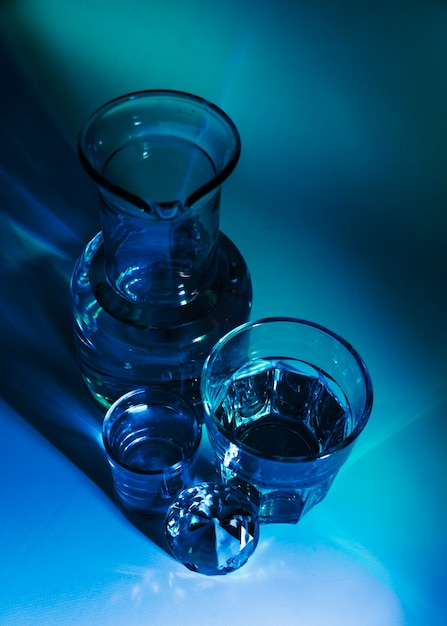 An elevated view of beaker; glasses and diamond on blue background Free Photo