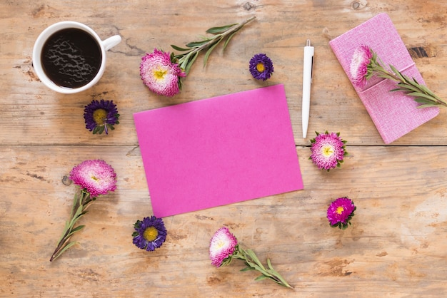Elevated view of beautiful flowers; blank pink paper; pen; diary and black tea on wooden surface Free Photo
