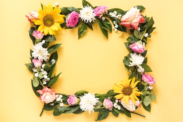 Elevated view of beautiful fresh flowers forming frame on yellow background Free Photo