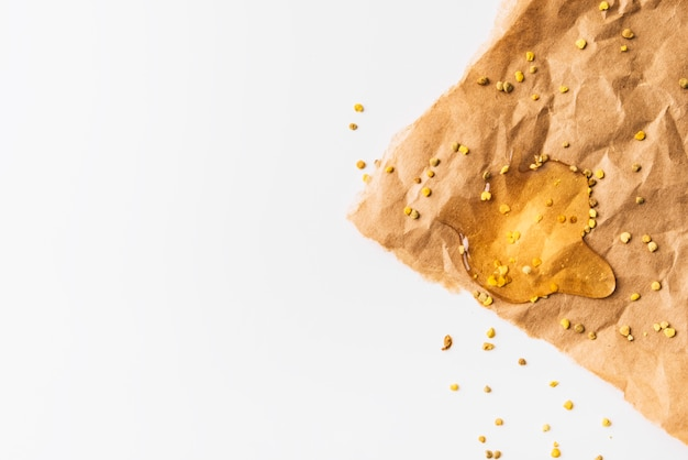 Elevated view of bee pollen seeds and honey on crumpled brown paper Free Photo
