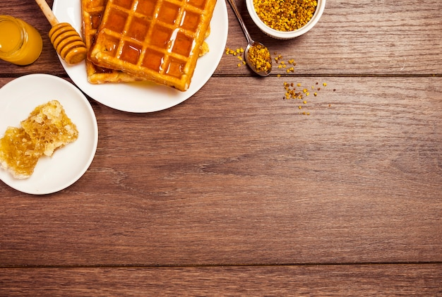 Elevated view of belgium waffle with honey and bee pollen on wooden textured Free Photo