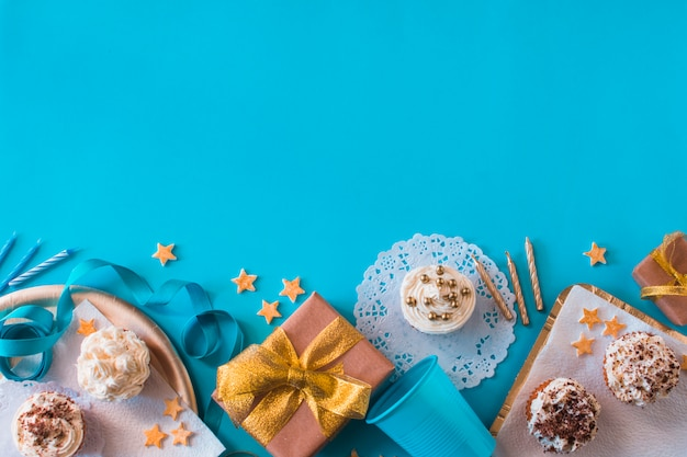 Elevated view of birthday gifts with muffins and candles on blue surface Free Photo